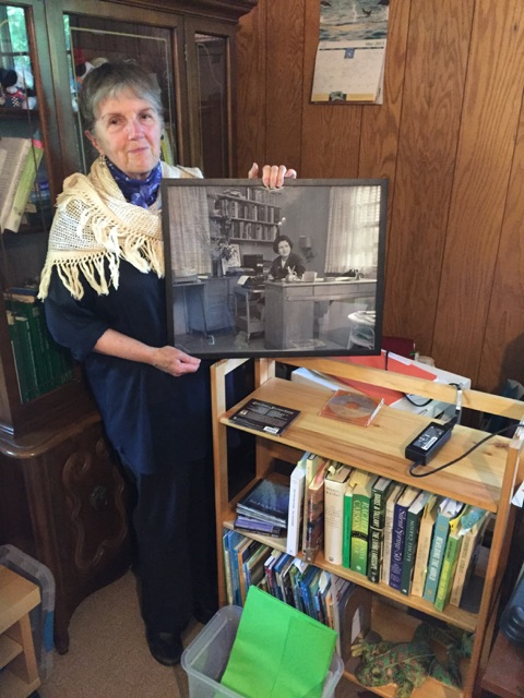 Dr. Diana Post standing where Rachel Carson had her desk. Post holds a framed picture of Carson sitting in the space more than 50 years ago. The hope is to make the picture a reality and restore this portion of Carson's office to the way she had it.